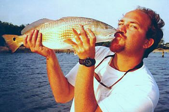 Captain J.R. Waits kissing redfish family fishing trips